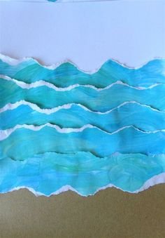 torn painted paper + sand paper. Have kids finger paint blue paper then tear into wave shapes