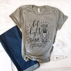 "Let Your Light Shine in this beautiful Christian t-shirt! This incredibly soft Christian shirt is the kind of shirt a girl buys two of—you'll love it that much. Featuring the words ""Let Your Light Shine Matthew 6:19,"" this beautiful women's t-shirt has been expertly designed to not"