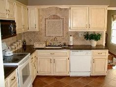 Antique (painted and stained) cabinets with white appliances. I love the  tile design