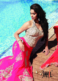 Sophisticated and stunning bridal finery look with A- line georgett neon red or deep peach color flowing lehenga enhanced with big gold zardozi and crystal motifs accentuated with Swarovski stone trimmed with exquisite encrusted with crystal and zardozi cutwork border worn over brocade silk elabrately embellished stone work corset blouse with matching fine net zardozi and stone encrusted cutwork border full length dupatta.