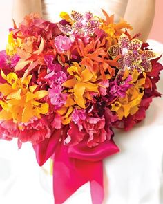 Audacious, hot colors just beg for a festive, outdoor summer wedding that's anything but traditional. This boisterous bouquet -- so big you'll need both hands! -- of sweetpeas, tulips, and orchids in flashy magentas, corals, and golds (tied with a wide raspberry satin sash) is the floral equivalent of a blast of sexy salsa music on a Miami Beach dance floor.