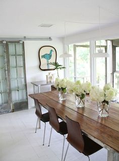via apartment therapy----Love the old farm table with the modern chairs, and the simple pendant lights.