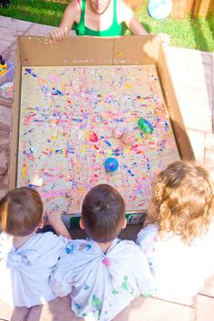 rolling painted balls over canvas - great way to create playroom art that involves the kids