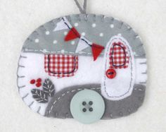 Grey and white vintage caravan Christmas ornament.  Vintage caravan trailer hanging ornament, handmade from felt and decorated with fabric scraps. With tiny felt bunting and buttons for the wheel and door knob, blanket stitched edges and a cotton loop for hanging.  Grey and white with red details.  The ornament is flat in shape, with a plain felt back. Size approx 3 x 2.5 inches / 7.5 x 6.5 cm  A perfect finishing touch for a little caravan, or the Christmas tree.  There are more caravan…