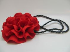 Dramatic red rose on a black beaded necklace. Handmade.   Red fabric rosette can be removed from necklace and converted to a pin.  Black beaded necklace is 16 inches.  - Part of our 'Queen of Hearts' collection  <3