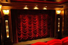 Fantastic red velvet curtains over the movie screen in a home theater.