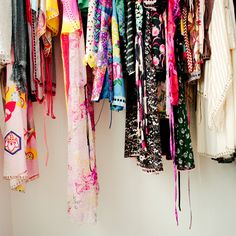Colorful clothing hung up against a white wall