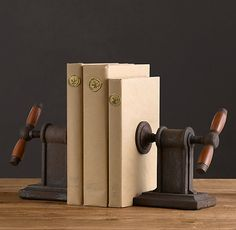 "Vise Bookends (Set of 2) VISE BOOKENDS (SET OF 2) $69 These iron-bodied vise bookends are exclusive to Restoration Hardware.  Plenty beefy enough to hold your 2-volume set of the OED Steel screws, propelled by turns of the smooth wooden handles, ensure a good grip on the heaviest novels Set of 2 DIMENSIONS 5¾""L x 5¼""W x 5¾""H"