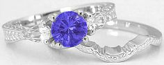 You will love the detailed carving on this tanzanite ring. For those of your who don't like diamonds or like a less expensive alternative, we have paired the round tanzanite with two pear cut white sapphires. This ring is unique and stunning. Found only at MyJewelrySource.
