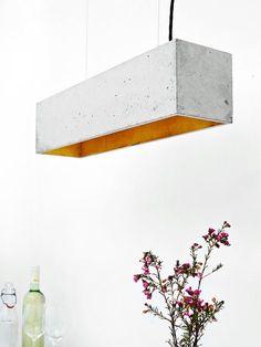 [B4] De rechthoekige hanglamp [B4] is gegoten uit een licht grijs beton. Het combineert edele goud met ruw beton in een tijdloze en elegante design
