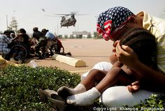 http://cdn.c.photoshelter.com/img-get/I0000E5Mk8fMO2rw/s/750/750/Hurricane-Katrina-131.jpg A mom covers her son as a Chinook helicopter land to evacuate people from the Ernest