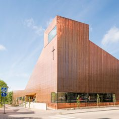 A copper-clad chapel and a faceted wooden sauna are among the four buildings…