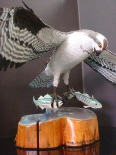 """BOB BARNES, Handcarved Wooden Osprey with Two Bass: A Unique Carving of the Rare Event of Osprey Swooping Down on His Prey of Two Striped Bass, Catching both at Once in His Talons. Barnes is a Self-taught Carver, who Lived off the Land in the New Jersey Wilderness. Mounted on Cypress log with Top Painted to Resemble The Chesapeake Bay where Event was Witnessed. Carved with Incredible Detail and Hand Painted. Carving Measuring 15"""" Tall with 27"""" Wing Span. (12000-18000)"""