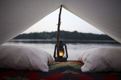 View of a lake and lantern from within a primitive tent