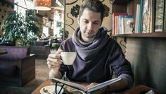 Un joven lee un libro en un café mientras bebe una taza de café.