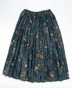 Jupe en toile de coton à fond vert turquoise imprimée à la planche de bois des ramages de fleurs stylisées dans le goût indien en rouge, jaune et marron avec des rehauts pinceautés de bleu. Le style des fleurs, la couleur du fond assez rare et les techniques d'impression correspondent à certaines impressions luxueuses réalisées dans les manufactures alsaciennes vers 1790. L'étoffe a été à l'origine utilisée en couverture piquée et réutilisée plus tard pour en faire une jupe