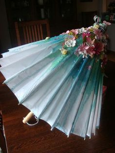 Umbrella that has been rained on by blue and turquoise water with May flowers beginning to blossom on the top