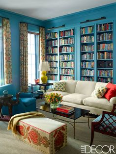 The library of a Manhattan home decorated by Katie Ridder. The sofa and club chair, both by Anthony Lawrence-Belfair, are covered in Holland & Sherry wools, the side table in the corner is one of a pair from Niall Smith Antiques, the camel side table is from John Rosselli Antiques, and the curtains are in a Quadrille fabric; the walls are painted in C2Paint Luxe in Bewilder.