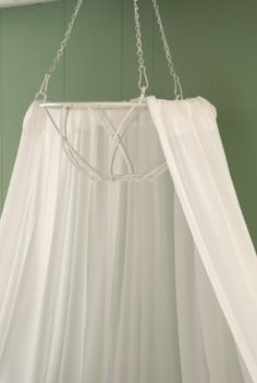 use a plant hanger basket to hold fabric or mosquito netting above bed