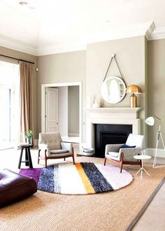 Bright living space with neutral walls, fireplace, round mirror, matching linen and wood armchairs, and circular striped area rug.