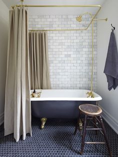 Hexagonal Bluestone marble floor tiles with classic honed Statuario Perla marble subway tiles for walls. Matte black paint makes a modern claw foot tub look vintage, and a linen shower curtain and dramatic brass rod give the tub presence.