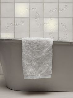 white tex-tiles behind bath with towel, three of the tiles are backlit. #tiles #transparant #white #translucent #porcelain #15x15 #bathroom #textiles #wall #decoration #led #imprint #relief #barbaravos #wallcovering #kitchen #shower #home #interior #design #glaze #backsplash #flower #pattern #coral #fabric #lace