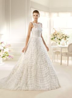 Milena - from the 2013 La Sposa bridal gown collection    Wow your guests with this stunner a-line dress with the soft wavy tiers that make up the skirt and the lace illusion top neckline on this dress