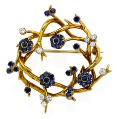 A sapphire and diamond brooch, by Tiffany & Co., of en tremblant design, the polished wreath decorated with four sapphire-set flowerheads, accented by circular-cut sapphire and brilliant-cut diamond detail, signed Tiffany & Co. Width 4.3 cm