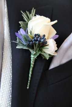 Groom's button-hole: traditional white rose centre with additional blue/lilac flowers to go with Navy Blue suit & cravat.  Best Man & Bride Father - similar button-holes but smaller and less ornate.