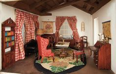 Shirley Temple's very own dollhouse has two interior rooms that are furnished with signed pieces of Tynietoy furnishings and with various carpets and curtains; Tynietoy furnishings include a fold-downable, faux marble top table, dining table, chest of drawers, buffet, red wing chair, six various chairs, and sofa.