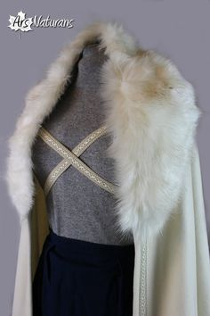 Nivalia, Pure Italian Wool Ivory Faux Fur Wedding Cloak Cross Closure.  This is great half-round 100% pure virgin wool cloak. Italian Wool is 100% natural, soft and very warm. It has a white and beige faux fur collar, and cream-white trim. It can be closed crossing it behind the back or with a simple knot or a bow at the front. No hood. Suitable to all sizes. Great cloak for medieval or pagan weddings, medieval characters or rituals.   Like all of our cloaks and dresses, you can request a…