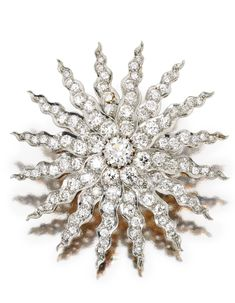 PLATINUM, GOLD AND DIAMOND BROOCH, CIRCA1900    Designed as a sunburst centered by an old European-cut diamond weighing approximately 1.20 carats, further set with numerous old European, old mine and single-cut diamonds weighing a total of approximately 7.60 carats, fitted with retractable pendant loop.