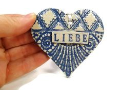 Listing is for one Ceramic LIEBE Heart Ornament. Each heart is hand sculpted, stamped and glazed by me. I use lace randomly to imprint the clay,