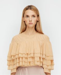 N-DUO's beige ruffle top is a feminine piece to compliment your ensembles day to night. The shirt features a scoop neckline and four tiers of ruffles that blends into the sleeves of the garment. Wear this piece with skinny jeans or the label's ruffle side skirt.