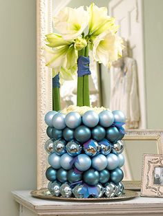 Holiday Welcome:  Place wet florist's foam in a vase with straight sides.  Insert flower arrangement into foam.  Thread string through ornament hangers and tie the lines of ornaments, layer by layer, around the vase, hot-gluing in place to secure