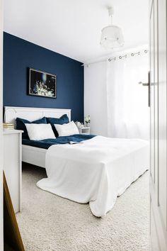 Głęboki granat ściany w tej sypialni jest wyrazistym tłem dla białego łóżka z wysokim wezgłowiem. Dzięki kontrastowemu zestawieniu biel mebli, narzuty i zasłon wydaje się jeszcze bielsza. Przytulności pokojowi nadaje miękka wykładzina w kolorze écru.