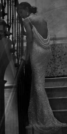 Layers of shimmering sequins cascade down this creamy textured gown for dramatic effect. This column silhouette finishes with an elegant cowl-back and puddle train.