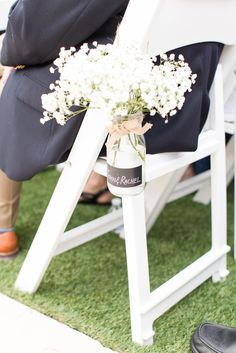 Cute idea for an aisle marker with white ceremony chairs--a vase tied with a blush bow and filled with white flowers. So cute and easy to do! Taken at THE SPRINGS Event Venue in Anna, TX. Book your free tour today! Photographer: Meggie Taylor Photography Simple wedding ceremony aisle markers, cute wedding ceremony aisle markers for a blush wedding, DIY wedding aisle markers