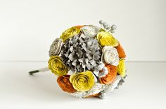 Autumn themed bridal bouquet with yellow, ivory and orange roses, gray hydrangeas, and silver berries. Everything is made from books!