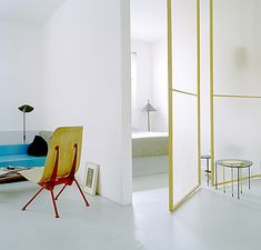 """The mostly white space highlights the colorful Jean Prouve vintage chair.  Mategot """"kangourou"""" tables on right?"""