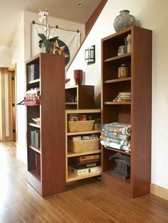 HOLY CRAP. Roll out bookshelves with more storage... under the stairs!