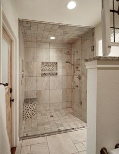 Low-threshold shower; note floor and ceiling tiles match. Universal design from Graf Developments.