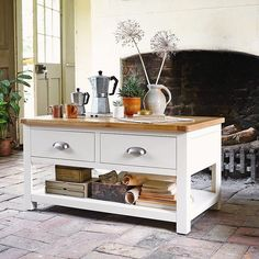 Cream Painted Coffee Table with drawers for living room storage. Styled in a country cottage with brick flooring and rustic wood fire, dried alliums, cacti and coffee kettles.