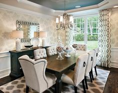 traditional and glamorous dining space : light fixture : area rug : buffet lamps : window treatments : upholstered chairs : accent color in ceiling tray