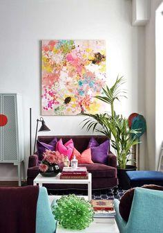 tableau à l'aquarelle, coussins en rose vif et lilas et fauteuils turquoise comme accent coloré dans le petit salon