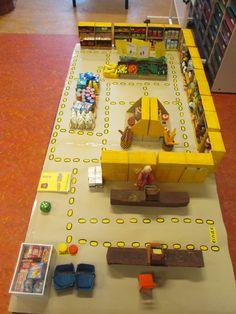 Het boodschappenspel. Op de supermarktspeeltafel is een parcours gemaakt. De kinderen hebben een boodschappenlijstje met 4 producten. Ze rollen de dobbelsteen en proberen een zo snel mogelijke route te volgen om hun 4 producten te pakken. Wie het eerst langs de kassa is, heeft het spel gewonnen. Nutsschool Maastricht.