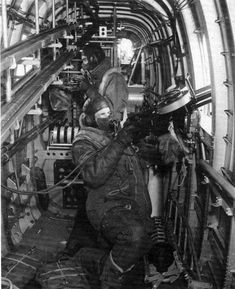 Beam gunners inside a Handley Page Halifax. Because of the large gunport openings, the interior of the Halifax could become numbingly cold, especially at 20,000 feet. Gunners wore special electrically heated flight suits which were plugged directly into the aircraft's electrical system. The leads can be seen running over the forward gunner's shoulder.
