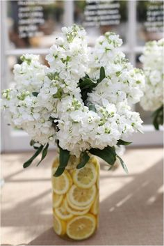 Adding a few arrangements here and there is always a nice touch. While at a wedding these are usually pretty elaborate, for an outdoor party they can be as simple as slicing those lemons from your backyard lemon tree and adding a few flowers from your garden to recreate something like this here, or even picking them up from your local grocery store after grabbing the BBQ supplies.
