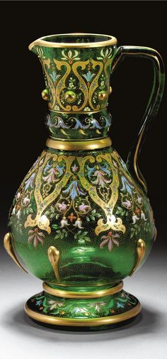 A Bohemian enamelled 'Persian-style' glass jug  perhaps Neuwelt, circa 1880 the green-tinted ovoid form with flared neck applied with six gilt 'jewels' or bosses, the lower half with six vertical gilt trails, below a collar and over a double-walled everted foot, painted with panels of scrolling foliage highlighted with gilding against a seeded gilt ground, applied square handle 28.5cm., 11¼in.