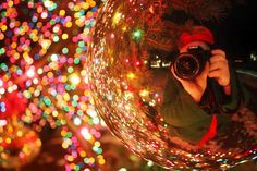 Self portrait in a Christmas ball ornament with bokeh lights in background